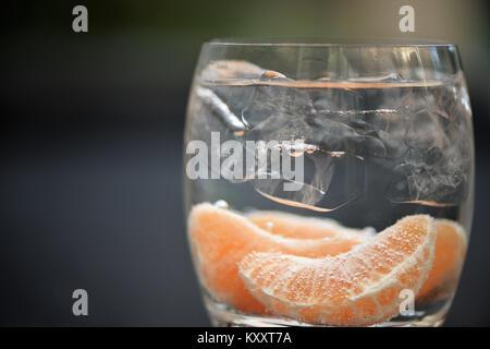 Essen und Trinken Makroaufnahmen Bild des gesunden orange Frucht in einem Glas Wasser mit Kohlensäure mit Blasen - Stockfoto