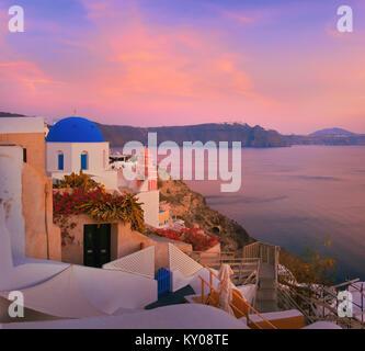 Das Dorf Oia, Santorini, Griechenland auf einen Sonnenaufgang mit lokalen Kirche mit Blick auf berühmte vulkanische - Stockfoto