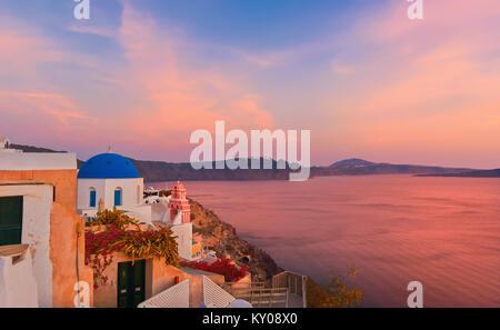 Das Dorf Oia, Santorini, Griechenland auf einen Sonnenaufgang mit lokalen Kirche mit Blick auf den berühmten Vulkan - Stockfoto
