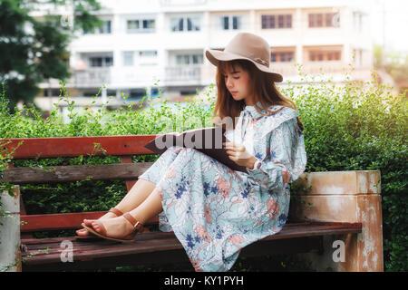 Junge asiatische Frau mit einem Buch auf der Bank im Park - Stockfoto