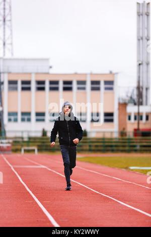 Athlet Asiatischen jungen Mann laufen auf der Rennbahn in Stadion. Gesunden, aktiven Lebensstil Konzept. - Stockfoto