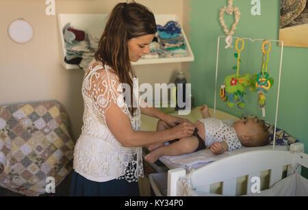 Die Mutter, die ihr Baby auf Wickeltisch - Stockfoto