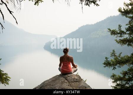 Passende Frau in Meditation Haltung auf dem Rand von einem Felsen sitzend - Stockfoto