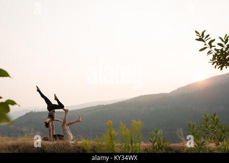 Sportliches Paar üben acro Yoga in einem üppigen Grün Masse - Stockfoto
