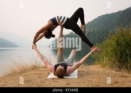 Fit Paar üben acro Yoga in einem üppigen Grün Masse - Stockfoto