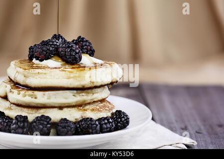Stapel von hausgemachte Pfannkuchen mit Brombeeren, schmelzende Butter und Sirup auf sie ausgegossen wird. Extrem - Stockfoto