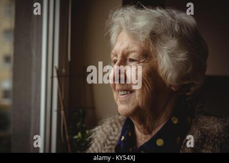 Lächelnde ältere Frau auf der Suche aus dem Fenster - Stockfoto