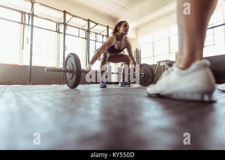 Muskulöse Frau anhebende Gewichte an einer Turnhalle. Passform weiblichen Athleten trainieren Sie im Health Club. - Stockfoto