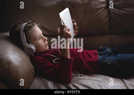 Junge mit digitalen Tablet mit Kopfhörern im Wohnzimmer - Stockfoto