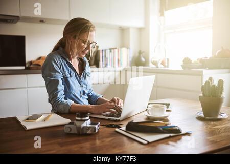 Junge Frau an ihrem Küchentisch sitzen zu Hause, in Ihrem kleinen Unternehmen mit einem Laptop gerichtet - Stockfoto