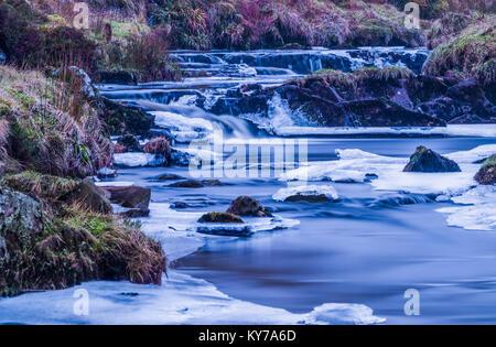 Eine gefrorene Schottischen Fluss oder im Winter brennen wie die Schneeschmelze wurde aus dem Moos bewachsen Ufern - Stockfoto