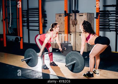 Athletische Frau Heben von schweren Hanteln auf Schultern in hellen geräumigen Fitnessraum - Stockfoto