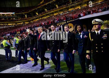 Us-Präsident Donald Trump Wellen, als er sich auf Wanderungen in das Feld für die NCAA College Football Endspiel - Stockfoto