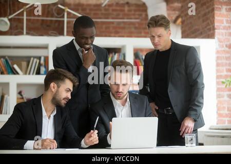 Executive gemischtrassiges Team in Anzügen Brainstorming über Project auf der Suche nach Laptop Bildschirm, diverse - Stockfoto