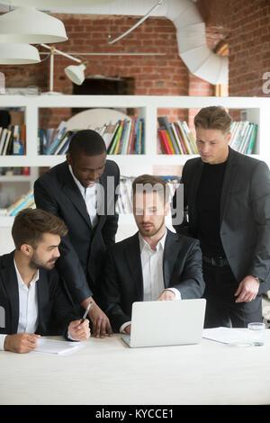 Afrikanische und kaukasische Geschäftsleute in Anzügen sprechen Ideen mit Laptop im Büro treffen, diverse Executive - Stockfoto