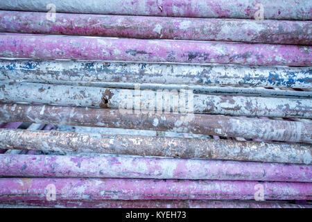 Haufen von schmutzigen lila Stahlrohre von Baumaterialien - Stockfoto