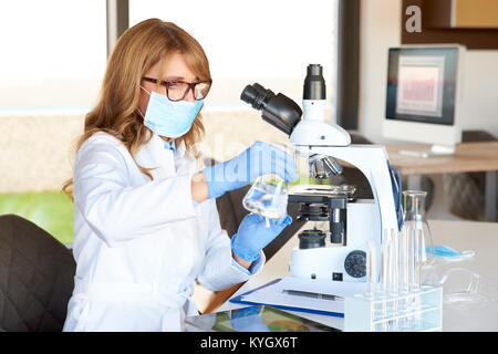 Im mittleren Alter Wissenschaftlerin sitzen vor dem Mikroskop und Arbeiten im Labor. - Stockfoto