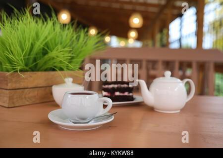 Wasserkocher mit einem Getränk und Nachtisch in einem Straßencafe. Tee in der Ket - Stockfoto