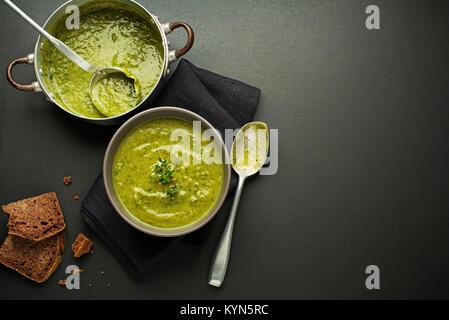 Frische, gesunde grüne Suppe auf schwarzem Hintergrund overhead zu schießen. - Stockfoto