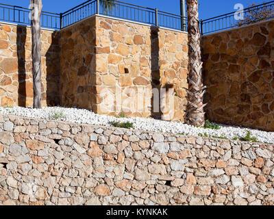 Steinmauer und weiße Kiesel Texturen mit Geländer und Palmen unter einem blauen Himmel in Andalusien Spanien - Stockfoto