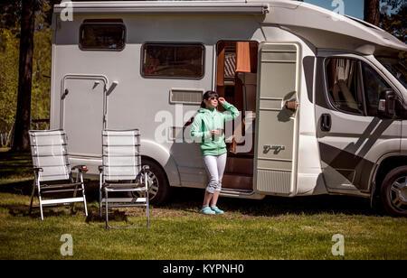 Frau steht mit einem Becher Kaffee in der Nähe der Camper. Caravan Auto Urlaub. Familie Urlaub Reisen, Urlaub im - Stockfoto