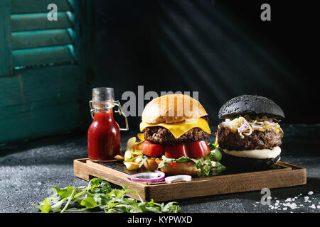 Hausgemachte schwarze und weiße Brötchen Hamburger mit Rindfleisch, Mozzarella, Sprossen, Rucola, auf hölzernen - Stockfoto