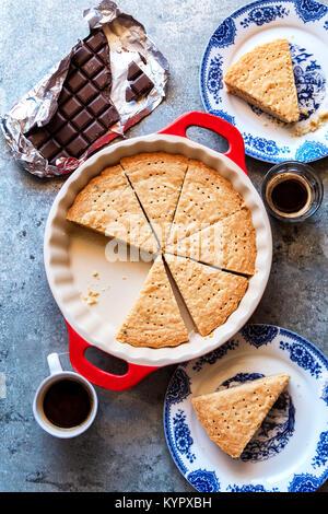 In Scheiben geschnitten Shortbread Cookies in einer Pfanne mit Tasse Kaffee und ein Stück Schokolade auf dem Tisch - Stockfoto