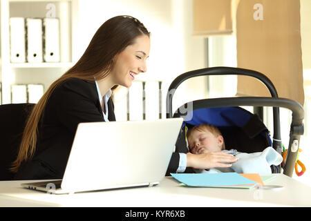 Glückliche Mutter arbeiten und kümmert sich um Ihr Baby Sohn im Büro - Stockfoto