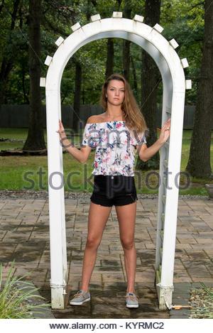972d93091b8 ... kurze weiße Kleider vor einem alten steinernen Kirche · Schöne Mädchen  in floralen Shirt und Shorts steht im Garten Home - Stockfoto