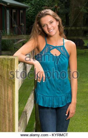 Schöne jugendlich Mädchen Posen in Jeans und Bluse on-farm-ländlichen Umgebung. - Stockfoto