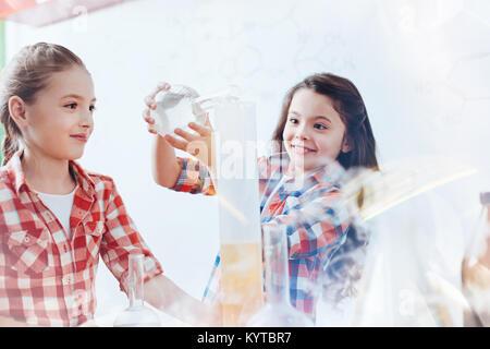 So aufgeregt, neue Sachen zu versuchen. Intelligente Mädchen lächelnd, während eine Flüssigkeit in ein Messglas - Stockfoto
