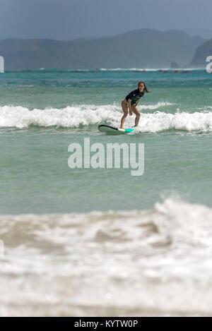 Pantau Mawun Lombok Indonesien. Junge Frau lernt, surfen Sie auf langen Board auf Lernende Wellen in paradiesischer - Stockfoto
