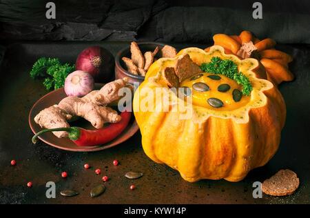 Würzige Kürbissuppe serviert in einem ausgehöhlten Kürbis auf dunklem Hintergrund. Die Suppe war gewürzt mit Chili, - Stockfoto