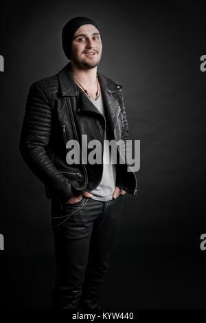 Wippschalter Serie. Ein Mann in der Lederjacke Porträt schwarzer Hintergrund - Stockfoto