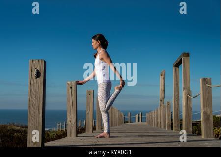 Frau, die ein Bein strecken durch das Meer. - Stockfoto