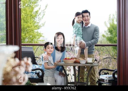 Glückliche Familien essen Frühstück auf der Terrasse - Stockfoto