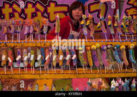 31.12.2017, Tokyo, Japan, Asien - eine junge Frau verkauft mehrfarbig Schoko Bananen zu einem Straßenrand in Harajuku. - Stockfoto