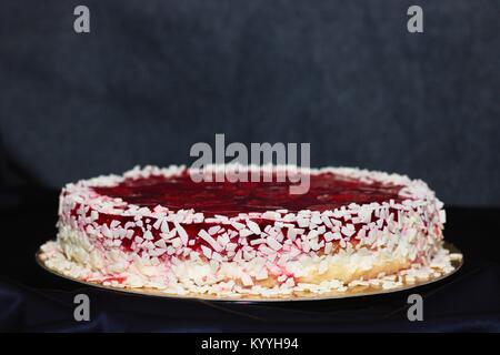 Erdbeer Gelee und weiße Schokolade Kuchen auf lila gekleidete Tabelle und grauer Hintergrund - Stockfoto