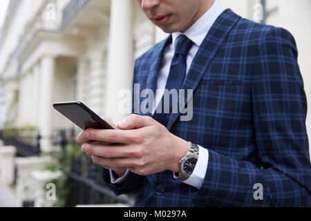 Junger Mann in Anzug mit Phone in Straße, mittlerer Abschnitt - Stockfoto
