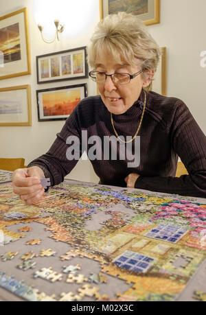 Pensionierte Dame/Frau Rentner tun ein Puzzle ENGLAND GROSSBRITANNIEN - Stockfoto