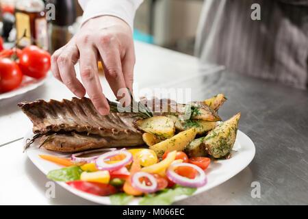 Der Küchenchef im Restaurant. Gegrillter Lammrücken mit Bratkartoffeln und frischem Gemüse. closeup - Stockfoto
