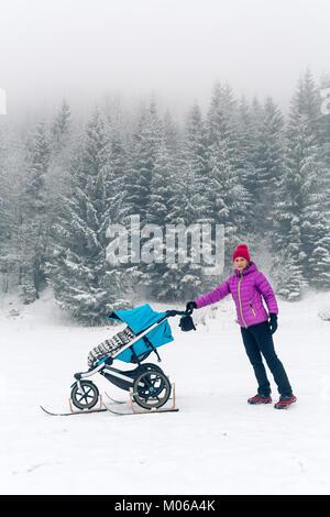 Mutter mit Baby Stroller genießen Mutterschaft im Winter Wald, in den Bergen. Joggen oder Walken Frau mit Schlitten - Stockfoto