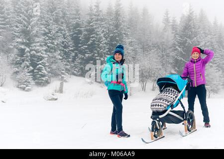Mutter mit Baby Stroller genießen Mutterschaft im Winter Wald mit Freundin oder Partner. Wandern oder Walken Frau - Stockfoto
