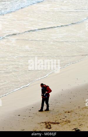 Ein Mann, Vater, Papa mit einem kleinen Baby oder Kind in ein Baby Carrier auf seine Brust entlang einem Sandstrand - Stockfoto