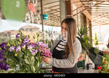 Small Business Konzept. Smilng weiblichen Blumengeschäft Blumen pflücken in einem Blumenladen. Horizontale Zusammensetzung
