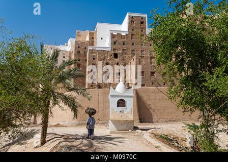 Ein Mann trägt eine schwere Last auf seinen Kopf in Shibam, ein UNESCO-Weltkulturerbe im Jemen am 8. Mai 2007. - Stockfoto