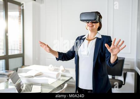 Ältere Frau mit VR-Brille Design ein Projekt vorzustellen, oder - Stockfoto