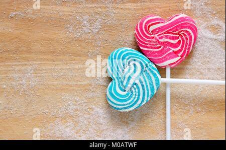 Bunte lollipop in Form von Herzen auf Holz Hintergrund - Stockfoto
