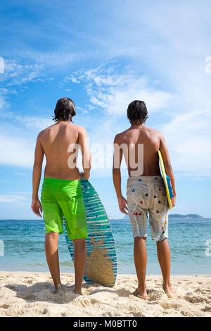 Jungen brasilianischen Männer stand mit skimboards am Ufer des Ipanema Beach in Rio de Janeiro, Brasilien - Stockfoto