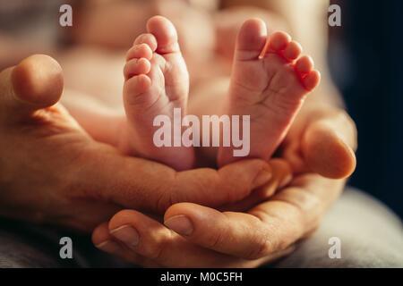 Neugeborenes Baby Beine in Mütter schöne Hand mit weichen Fokus auf und Schuhen Fuß